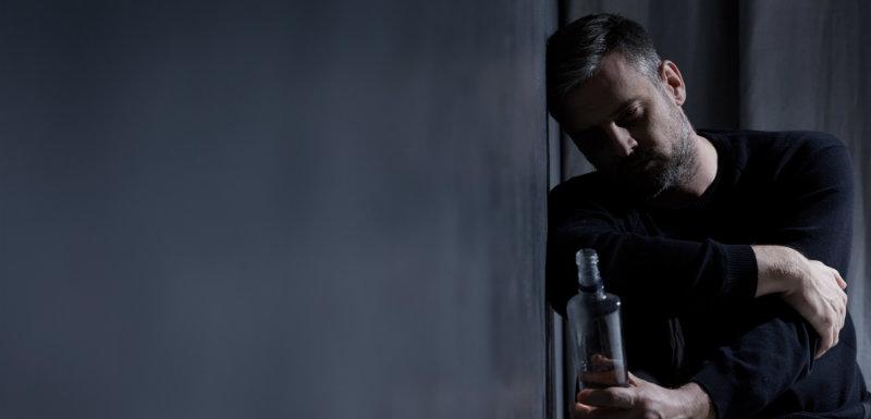 dépendance à l'alcool - homme tenant une bouteille d'alcool