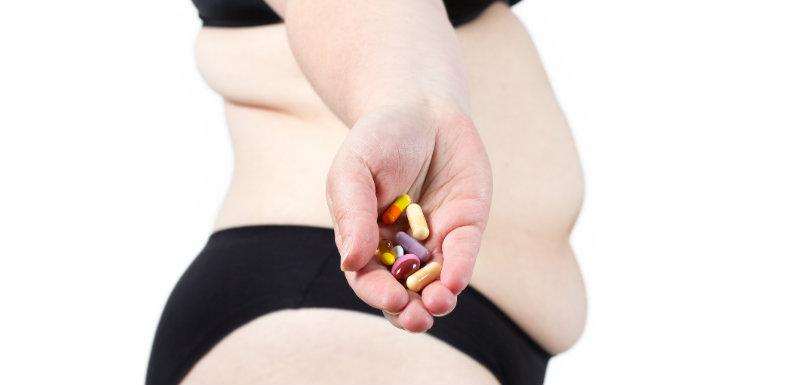 Femme en surpoids tenant des médicaments antidépresseurs dans sa main