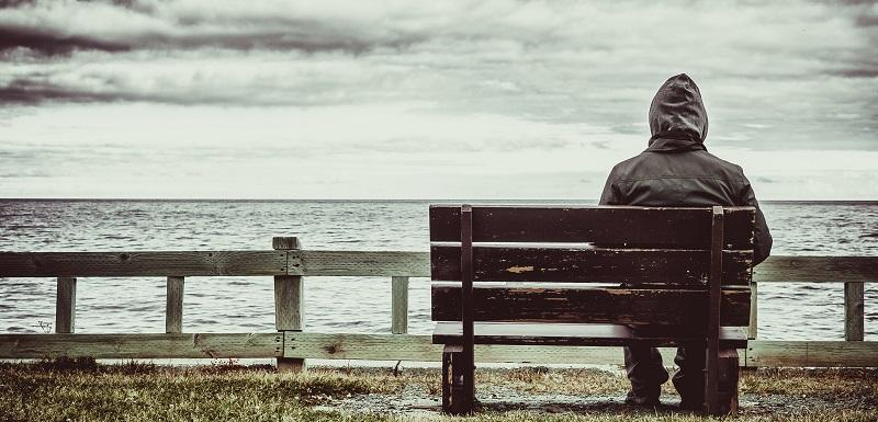 Un homme assis sur un banc avec une vue sur la mer.